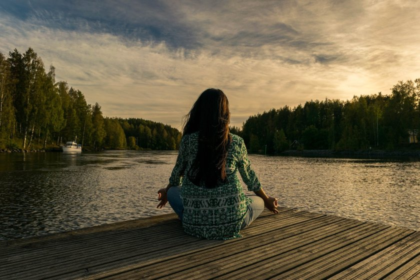 Woman meditating next to lake