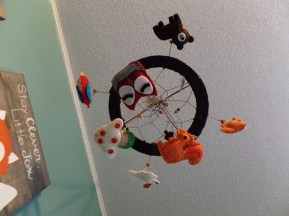 Mobile was made by my mom, sister and me. We used little felt animals from Hobby Lobby, I think, and made a dream-catcher feature in the round itself.