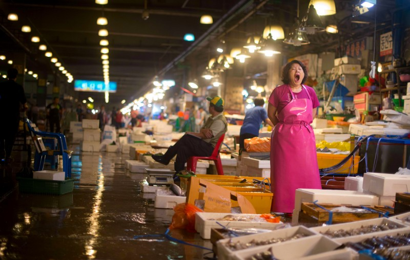 A fishmonger (R) yawns as she stands at her stall in the Noryangjin Wholesale Fish Market in Seoul early on July 4, 2013. Established in 1927, the Noryangjin Fish Market runs 24 hours a day and is the largest in Seoul. Selling flounder, sea bass, rockfish, king crab, abalone, octopus and oysters, among others, the market supplies most of the Seoul capital area which encompases the Incheon metropolis and Gyeonggi province to form the world's second largest metropolitan area with over 25.6 million people. Buyers spend almost one million US dollars daily attending raucous early morning auctions that pit wholesale buyers against each other as they vie for the days catch. A popular tourist destination, visitors can select fish which is then prepared, to be eaten raw, by various restaurants flanking some 700 stalls. On July 2 the Korean National Assembly amended its fisheries law to help curb illegal fishing by increasing penalties to a maximum of three times the value of the fish caught. AFP PHOTO / Ed JonesEd Jones/AFP/Getty Images