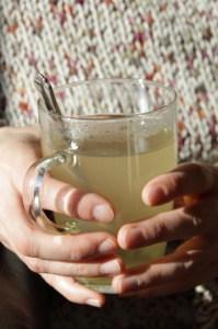 Hands holding lemon honey drink