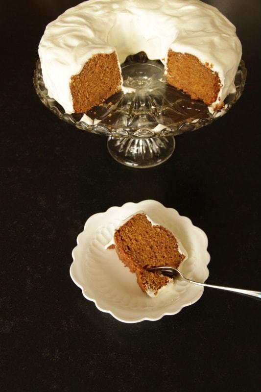 Slice of carrot cake, cake on platter in background