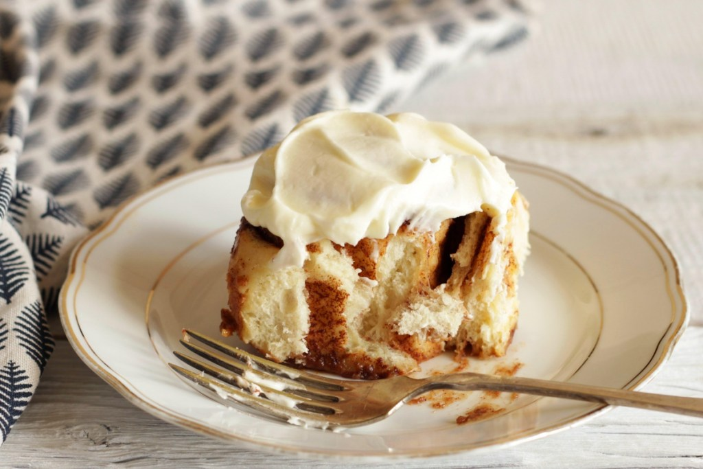 cinnamon roll on plate with fork
