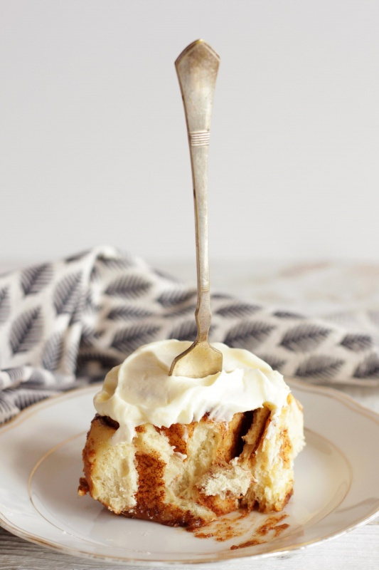 cinnamon roll stuck vertically with a fork
