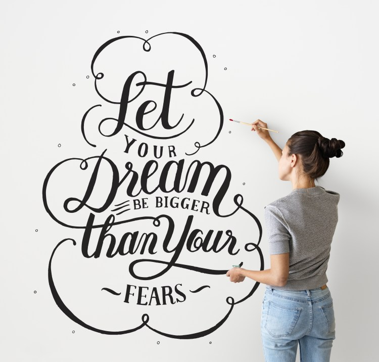 How to be more positive - Female artist writing a life motivation quote on the wall