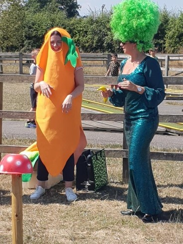 Happy Days: 5 great animal attractions in Southern England. Image of woman laughing wearing a carrot costume, Standing next to a woman in a long green sparkly dress and green wig holding a banana