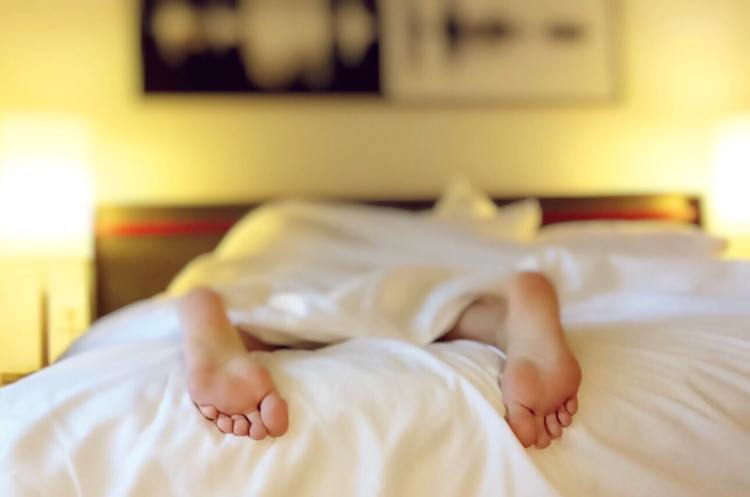10 ways to slow signs of ageing around your eyes without using an eyecream. Image of a woman's feet sticking out of the end of a bed