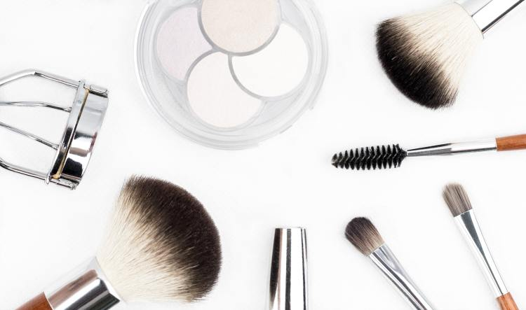 10 ways to slow signs of ageing around your eyes without using an eyecream. Image of make up brushes, eyelash curlers and an eyeshadow pallet on a white background