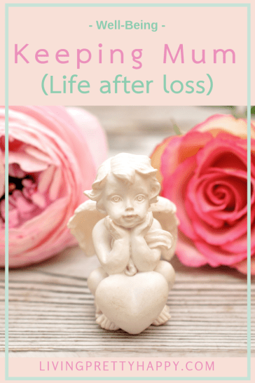 Keeping mum (Life after loss) Pinterest graphic displaying post title on a background image of a little white cherub angel on a wooden surface with two pink flowers laying down flat behind it. livingprettyhappy.com well-being