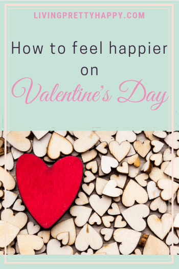 How to feel happier on Valentine's Day. Pinterest graphic displaying post title on a background image of lots of little wooden hearts with one big red wooden heart on top. Livingprettyhappy.com