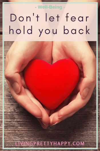 Don't let fear hold you back. Pinterest graphic displaying post title on a background image of a woman's hands holding a foam red heart over a wooden table. well-being. livingprettyhappy.com