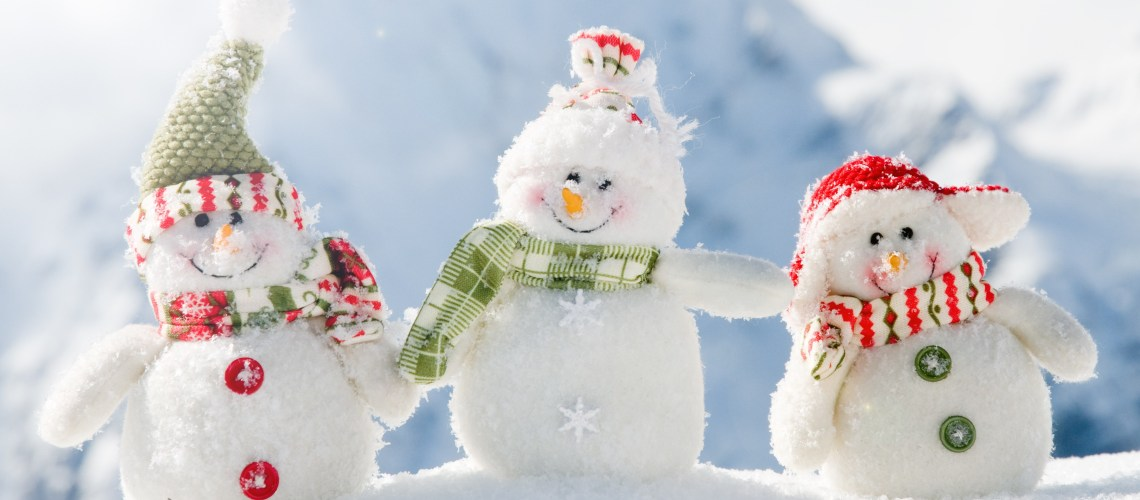How to have a happier Christmas: Image of 3 toy snowmen smiling in the snow with a snow covered mountain in the background