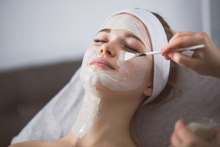 For the scrub of it: why should you exfoliate and how to do it right! Beautician applying anzymatic peeling on woman's face in spa