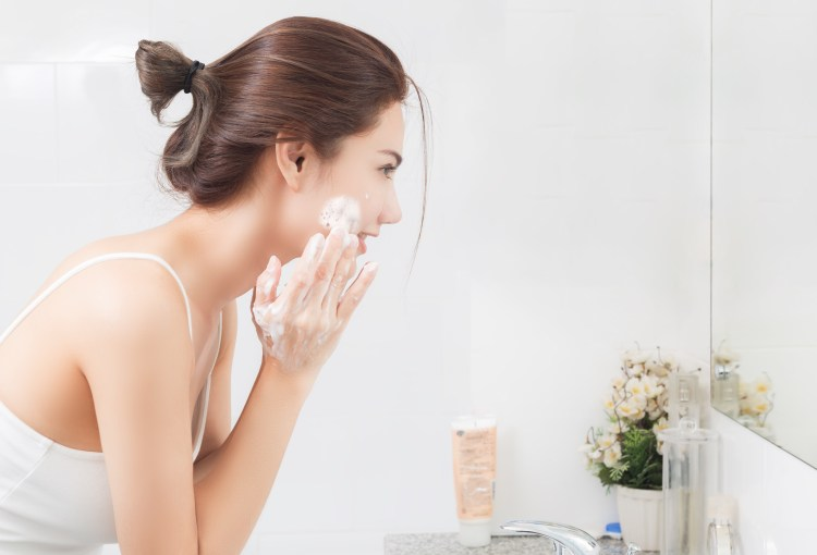 For the scrub of it: Why should you exfoliate and how to do it right. Woman happy cleanses the skin with foam in bathroom.