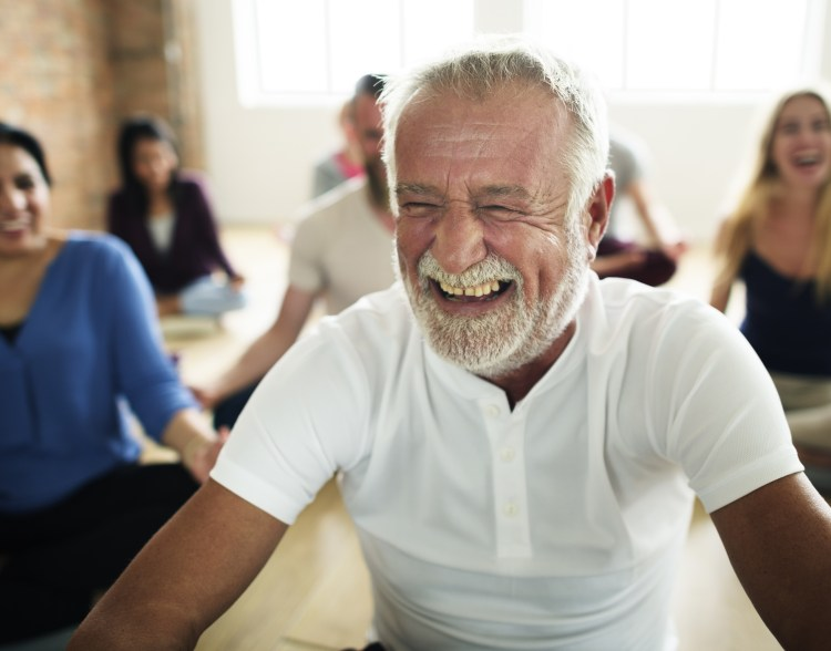 5 Ways exercise makes you happy.  Image of a relaxed smiling older gentleman taking part in a yoga meditation class