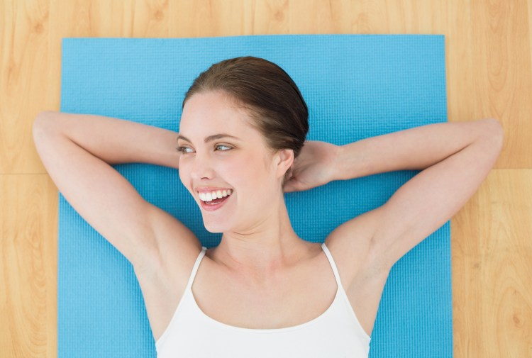 5 Ways exercise can make you happy. Image of cheerful woman lying on an exercise mat