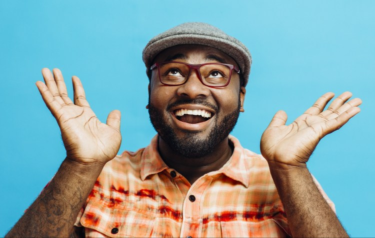 Improving well-being: The key to being happy?  Image of man wearing a flat cap and glasses, smiling, looking upwards and holding up his hands in a happy gesture