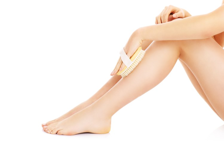 For the scrub of it! Why should you exfoliate and how to do it right. Image of a woman's bare legs holding a body brush on them over a white background
