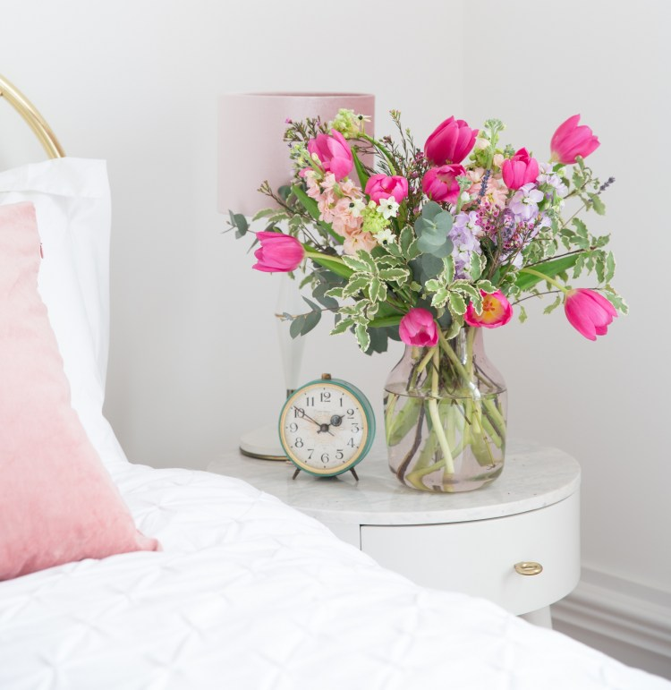 Blooming lovely: the positive power of flowers. Image of a vase of flowers on a bedside table