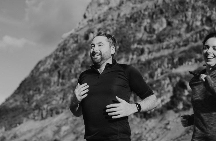 5 Ways exercise makes you happy.  Black and white image of a man exercising smiling with a mountain behind him