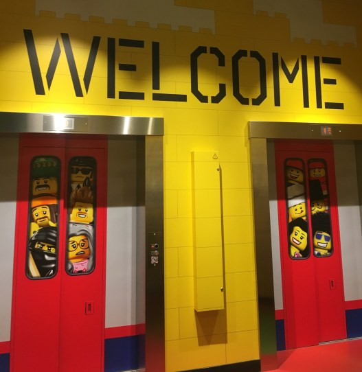 Happy Days: Legoland Discovery Centre Birmingham.  Image 2 lifts displaying pictures of Lego characters with the words WELCOME above it at Legoland Discovery Centre Birmingham