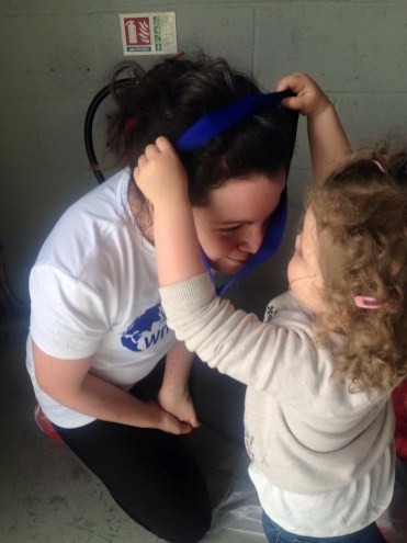 Why I run. Image of little girl putting medal over woman's head