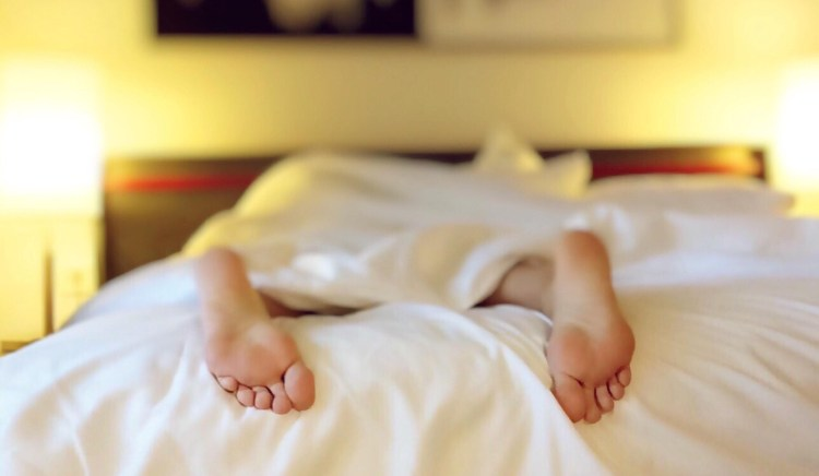 5 Useful ways mindfulness helps in your everyday life. Image of a person's bare feet protruding out of the end of the bed