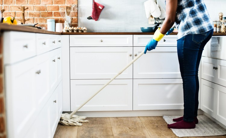 Exercise Hacks: How to be fitter without really trying.  Image of adult mopping the kitchen floor