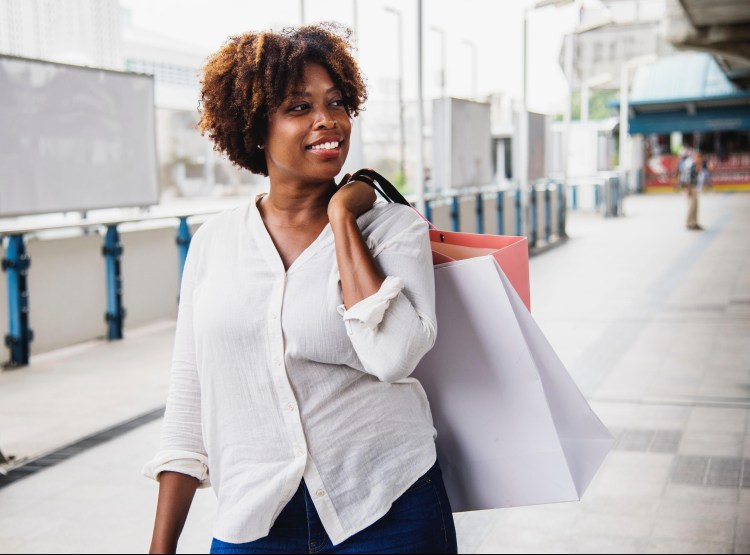 Exercise Hacks: How to be fitter without really trying.  Image of woman walking carrying shopping bags and smiling