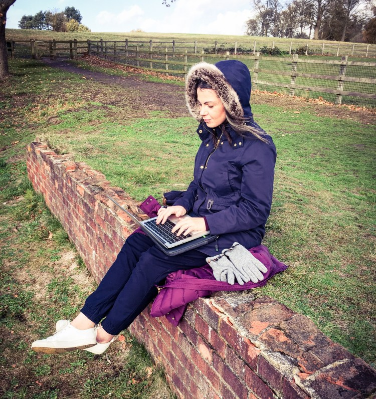 The Sunshine Blogger Award. Image of Alex Grace sitting on a wall typing on a Mac Book