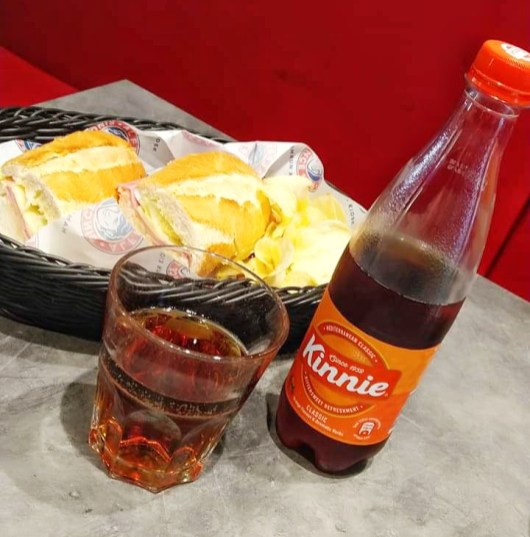 10 Things you should know about Malta - Going to Malta - 10 things you should know. Image of Kinnie bottle next to a glass of Kinnie with some food behind it