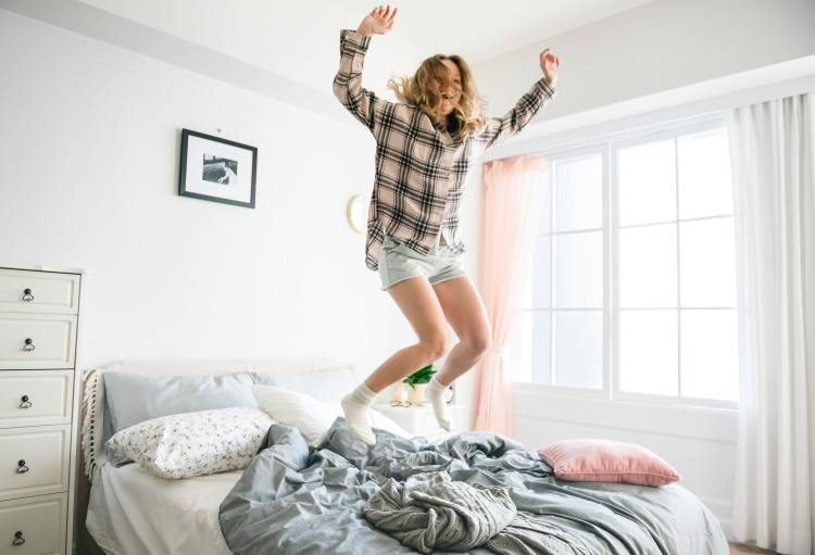 Livingprettyhappy.com young happy woman jumping up and down on an unmade bed