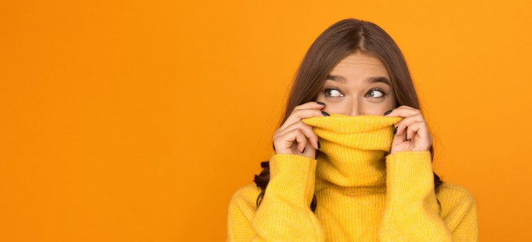 I'm new here: 10 ways to feel more confident in new situations. Image of woman hiding her face partially in her yellow jumper against an orange background