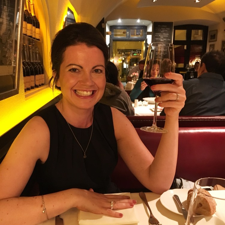 Understanding yourself: How EMDR Therapy helped me develop as a person.  Image of Alex Grace smiling in a restaurant holding a glass of red wine happy