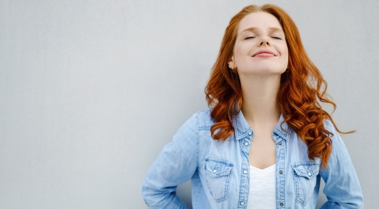 Maintaining the (inner) peace: 5 products to help calm & increase your well-being. Image of a young red-haired woman leaning against the wall, eyes closed and smiling looking at peace.
