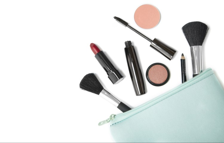 How to do your makeup in only 5 minutes. Image of peppermint makeup bag with various makeup products and brushes coming out of it