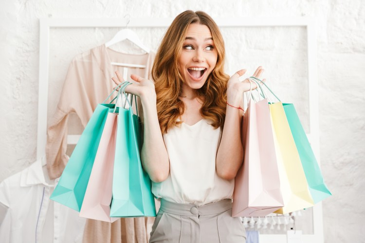 How can clothes make you happy? Plus expert tips for more successful shopping. Image of Happy young woman holding shopping bags while standing at the clothing store