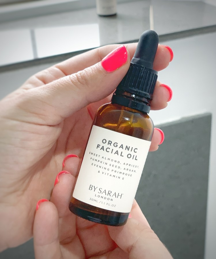 By Sarah London Organic Facial Oil Review - Image of hands holding a 30ml product