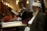 An elderly man reads verses of the Quran, Islam's holy book, on the first day of the fasting month of Ramadaan in the grand Mosque in the old city of Sanaa, Yemen