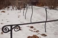 Handrail beside snowy path.
