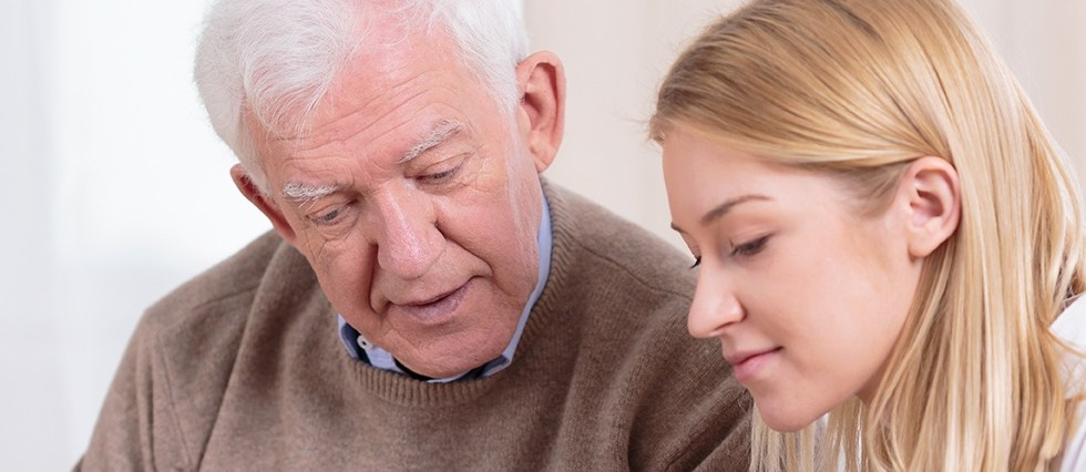 Older man and occupational therapist consulting a report together.