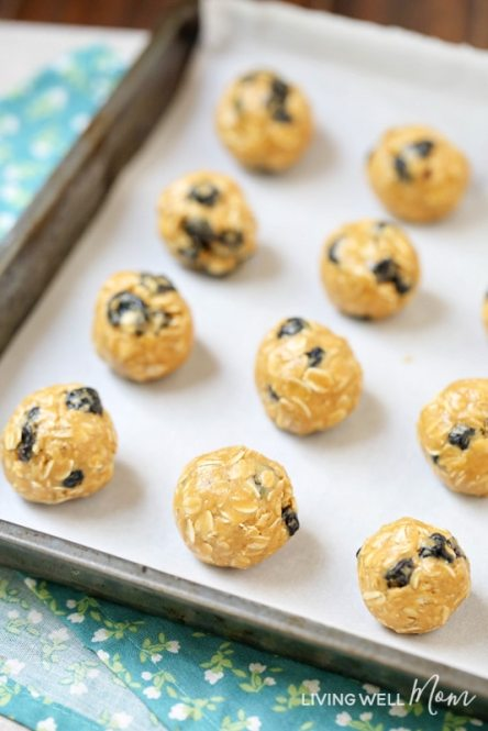 easy no bake blueberry energy balls on parchment paper cookie sheet