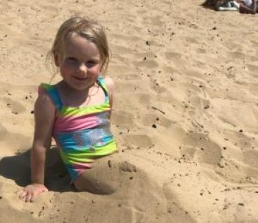 Emmeline with legs buried in the sand