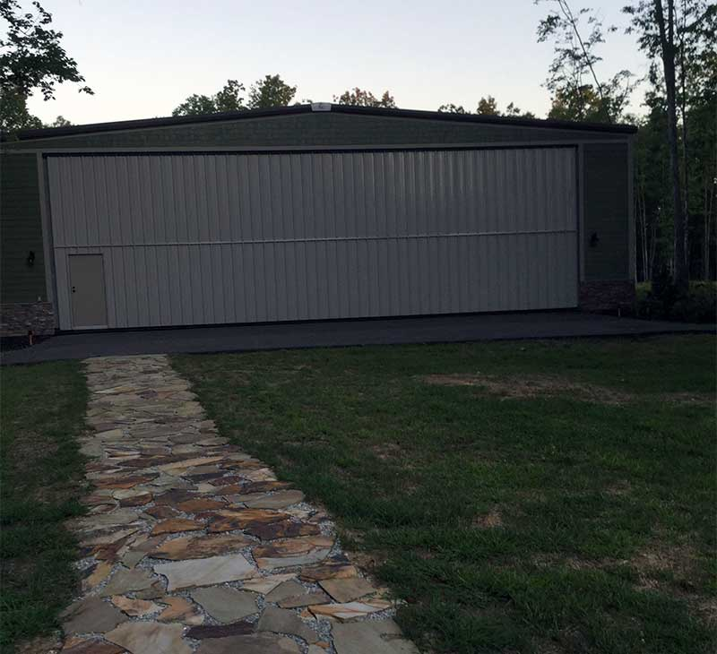 A stone paved walkway leads from the back of the Rogers home to his hangar.