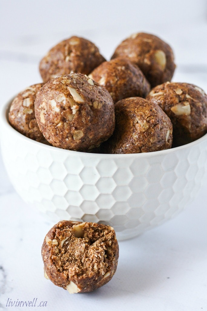 A white bowl filled with almond espresso energy bites with one off to the side with a big bite taken out