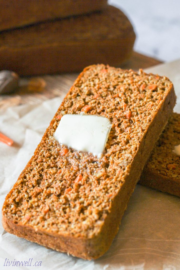 A warm piece of gluten free carrot cake with a dollop of melting butter on top