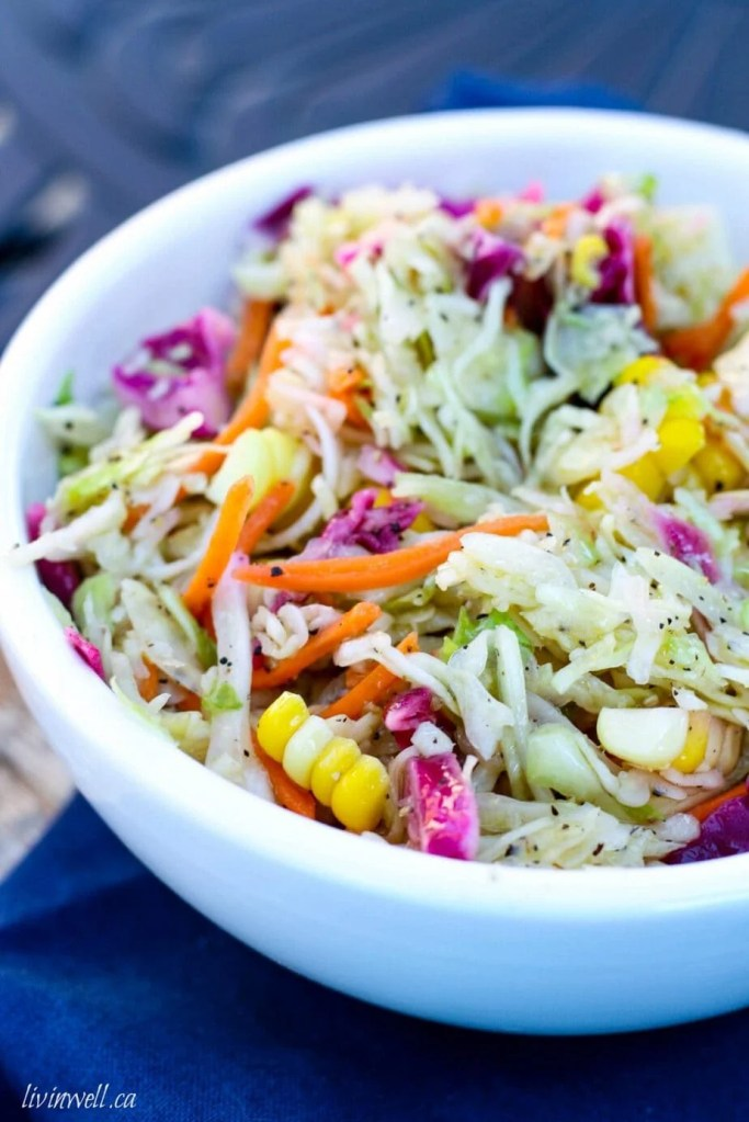 Homemeade coleslaw made with an oil and vinegar base held in a crisp white bowl over a royal blue napkin
