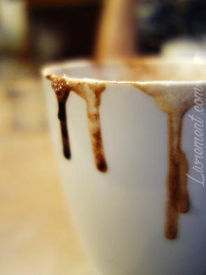 Gouttes de chocolat chaud qui coulent le long d'une tasse