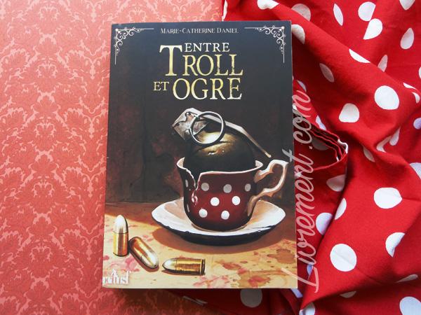 """Le roman """"entre troll et ogre"""" de Marie-Catherine Daniel est mis en scène sur du papier typé """"tapisserie"""" et du tissu rouge à pois blancs qui reprennent des éléments de la couverture du livre"""