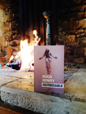 """Le roman """"Outresable"""" de Hugh Howey pris en photo à côté d'un feu de cheminée"""