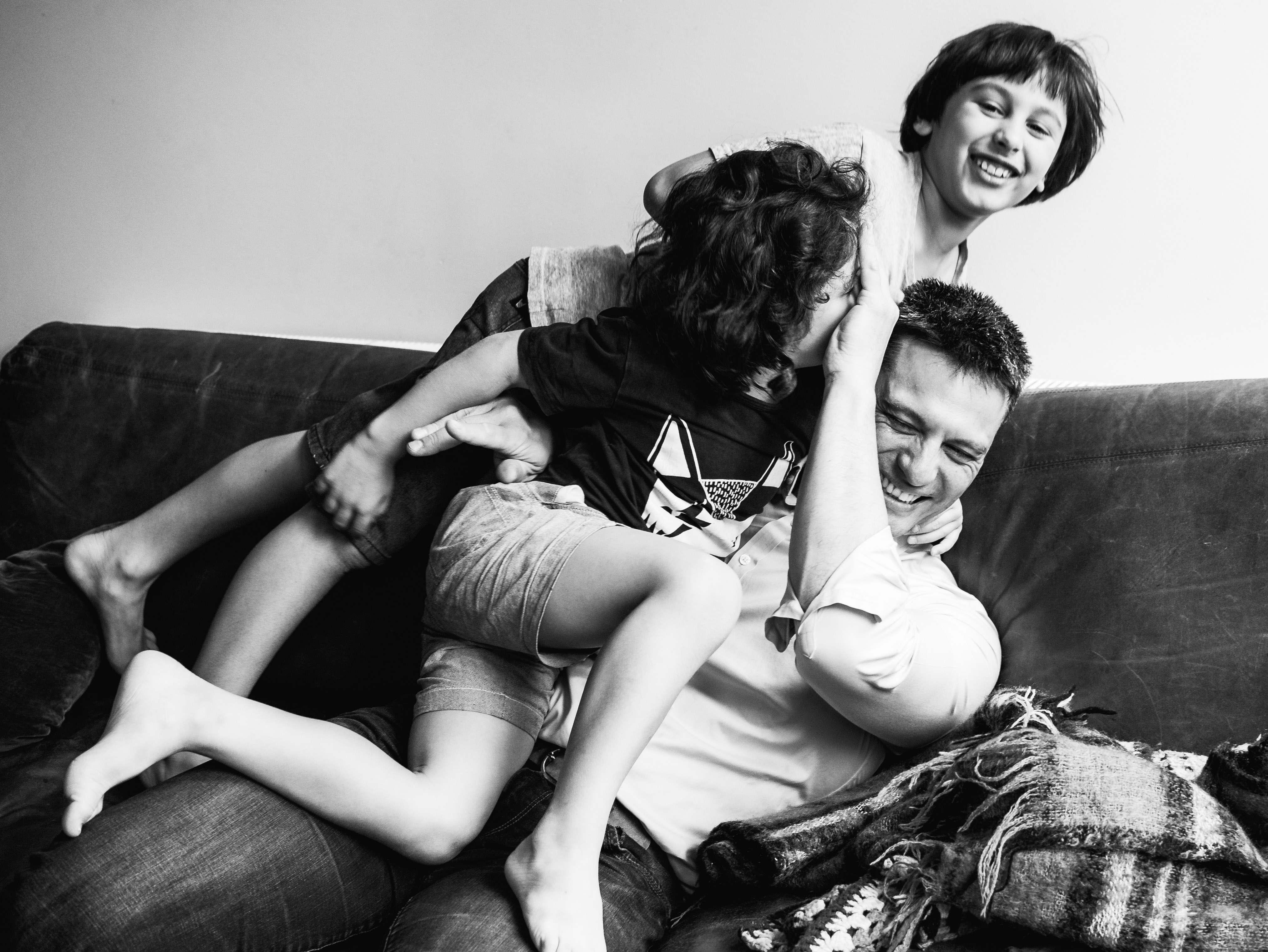 photograph of boys wrestling their father on a couch/sofa in Carlton North, Melbourne, Australia
